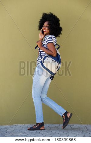 Full Length Woman Talking On Mobile Phone And Walking With Bag