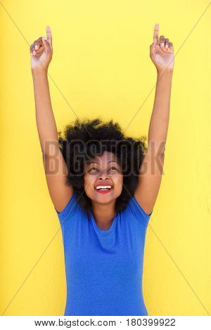 Happy Woman Laughing With Arms Raised Pointing Up
