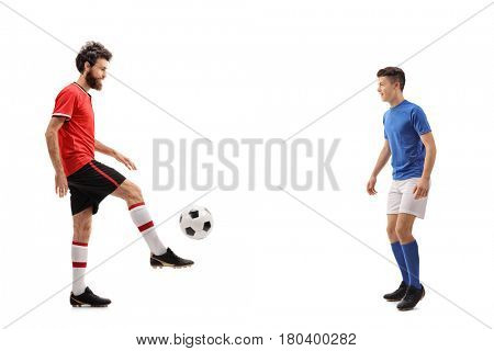 Full length profile shot of a father and his son dressed in jerseys passing a football isolated on white background