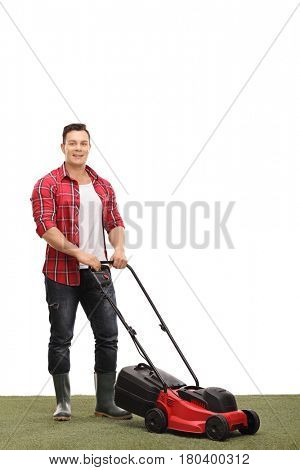 Full length portrait of a young gardener with a lawnmower isolated on white background