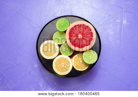 Cut Lemons, Limes And Grapefruit In Glass Bowl On Lilac Background. Top View