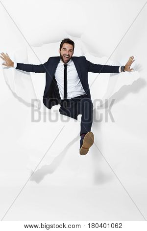 Businessman emerging from torn paper portrait studio