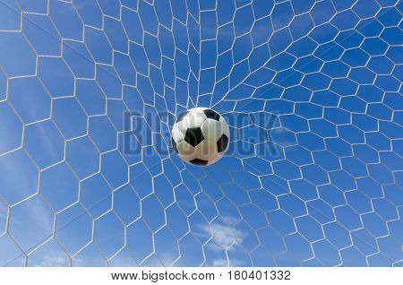 Soccer football in Goal net with Blue sky field.