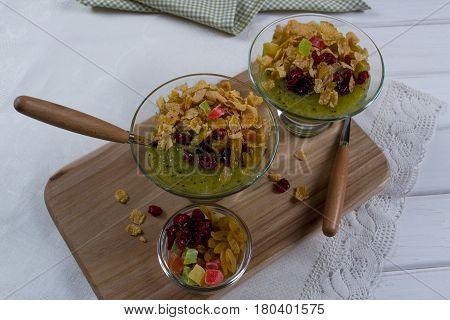 Healthy breakfast, summer dessert with smoothie kiwi, corn flakes and dried fruits in a glassware