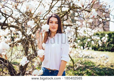 Beauty Woman Standing On Background Magnolia Blossoming Flowers. Spring Season