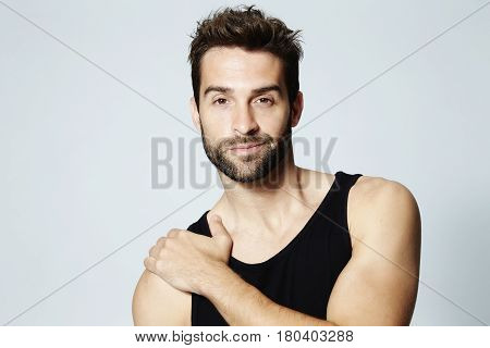 Vest man with stubble posing in studio