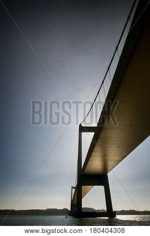 Beautiful suspension bridge from below and a small fishing boat. Blue and cold April morning in Denmark.