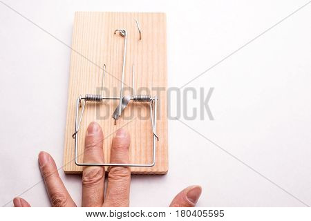 Finger caught by the mousetrap device on white background