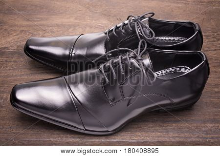 Sideways black leather shoes on a wooden floor