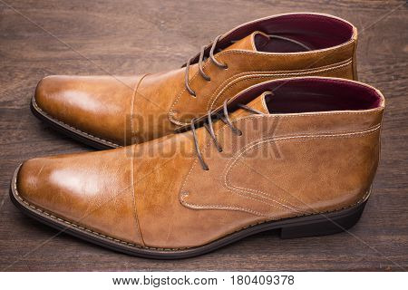 Sideways brown chukka boots on a wooden floor