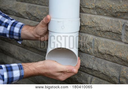 Rain Gutter Downspouts & Downpipes Installation with Contractor Hands. Cleaning and Repair.