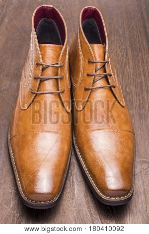 Front view of brown chukka boots on a a wooden floor