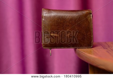 The brown leather wallet on edge of a table