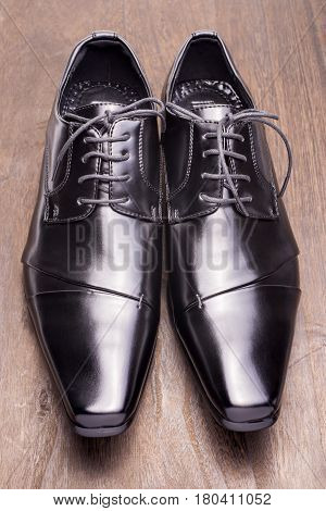 Front view of black leather shoes on a wooden floor