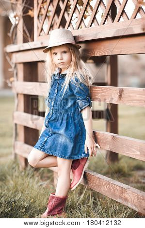 Stylish baby girl 4-5 year old wearing stylish denim dress in park. Looking at camera. Childhood.