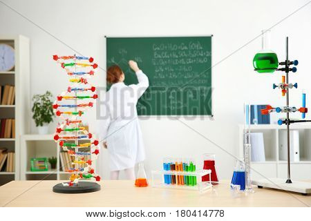 Workplace with different tools and school girl writing on blackboard in chemistry class