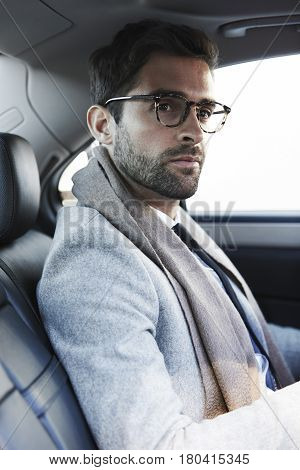 Stubble guy with eyeglasses in car taxi
