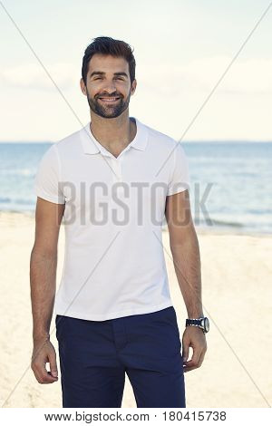 Portrait of man on holiday smiling on beach