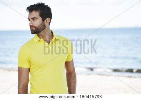 Man on holiday on beach in yellow shirt