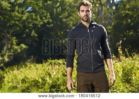 Handsome hiker looking at camera beautiful nature
