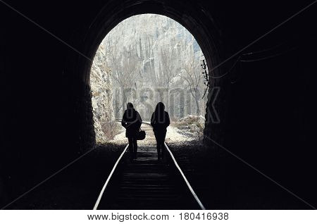 Two girls walk the railway and get out from tunnel. Light on the end of the tunnel