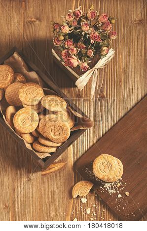 Low key still life of cookies in the box and dry roses on wooden board. Biscuits stack and one broken cookie with crumbs on cutting board.