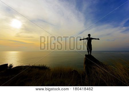 Silhouette of a man with raised-up arms at the beautiful sunset traveller man stands on a stone of sea stony coast