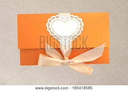 Orange gift envelope tied with a pink ribbon. paper texture