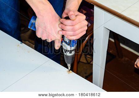 Carpenter Drilling A Hole In A Chipboard