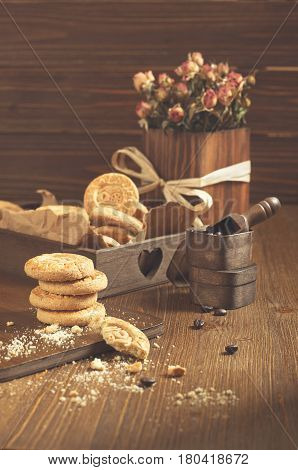 Side view of cookies in the box and dry roses on wooden board. Biscuits stack and one broken cookie with crumbs on cutting board. Coffee beans in small wooden box