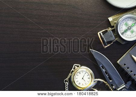 Pocket knife with compasspaperpencilnotebookpocket watchropemagnifying glass on black wood background.