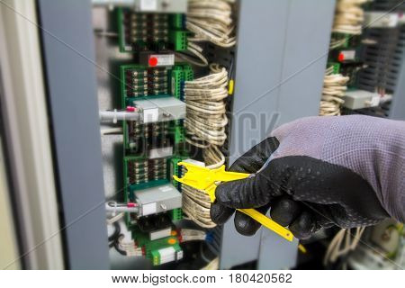 Fuse removal tool, hand of technician during replace the fuse in junction box.