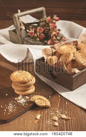 Side view of cookies in the box and dry roses on wooden board. Biscuits stack and one broken cookie with crumbs on cutting board.