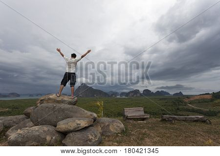 Man standing on big stone holding his hand up and see landscape view in bad weather day