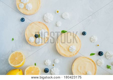 Individual Lemon Curd Tarts With Blueberry Jam Meringue And Basil Leaves On A White Stone Background