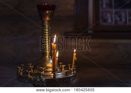 Burning church candles on a candlestick. In the background is a wooden wall. Copy-space.