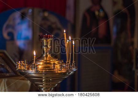 Burning church candles on a candlestick. In the background is the interior of the church the church. Copy-space.