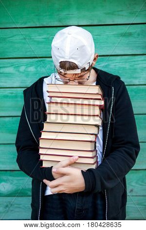 Tired Teenager with a Books by the Wooden Wall Background