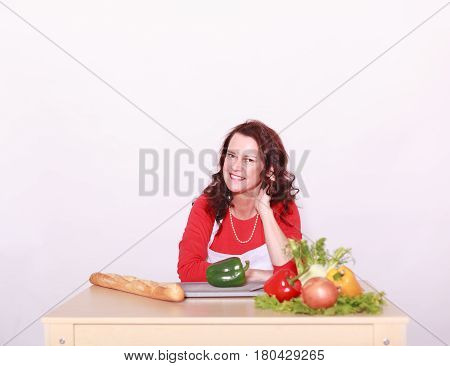 Middle-aged woman sits in front of the vegetable and salad and laughing looking at the camera.