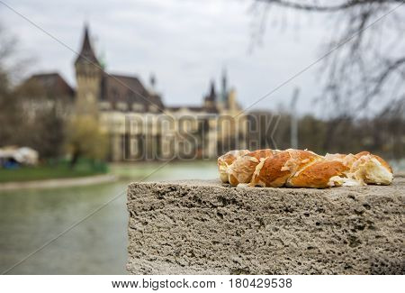 Soft pretzel, lying on the bridge parapet on the background of the castle