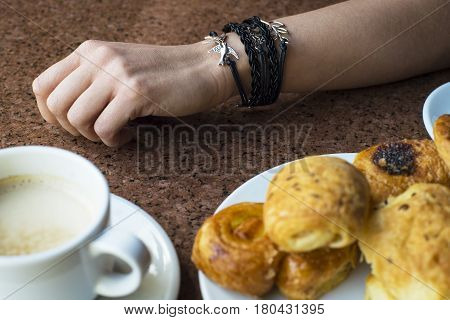 A Woman's Hand With A Coffee On The Table. Coffee With Pastry On The Table.