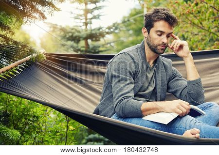 Man relaxing on hammock with book sun down