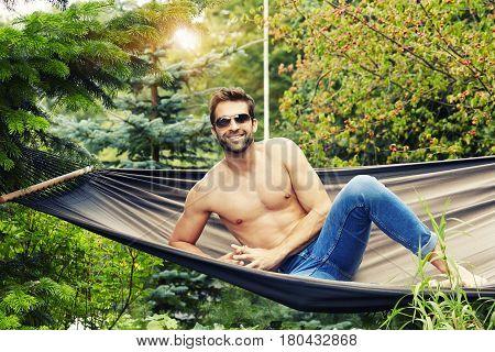 Shirtless dude in hammock looking at camera smiling