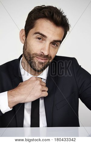 Businessman with stubble looking at camera studio shot