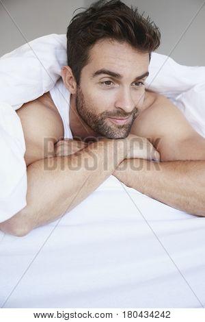 Man relaxing in bed under duvet in bedroom