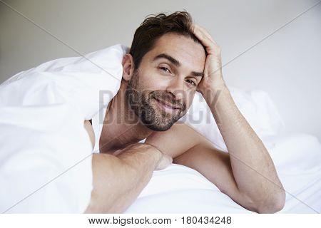 Man relaxing under duvet portrait in bedroom