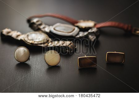 men's accessories. Cuff and watch in wooden background