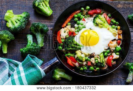 Frying Pan With Fried Egg And A Vegetable Mixture: Peanuts, Broccoli, Paprika And Frozen Broccoli On