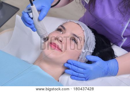 Young beautiful woman gets professional rejuvenation facial skin treatment in a professional beauty clinic
