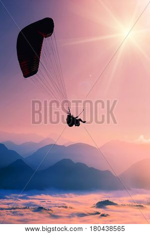 Paraglide silhouette flying over misty mountain valley.